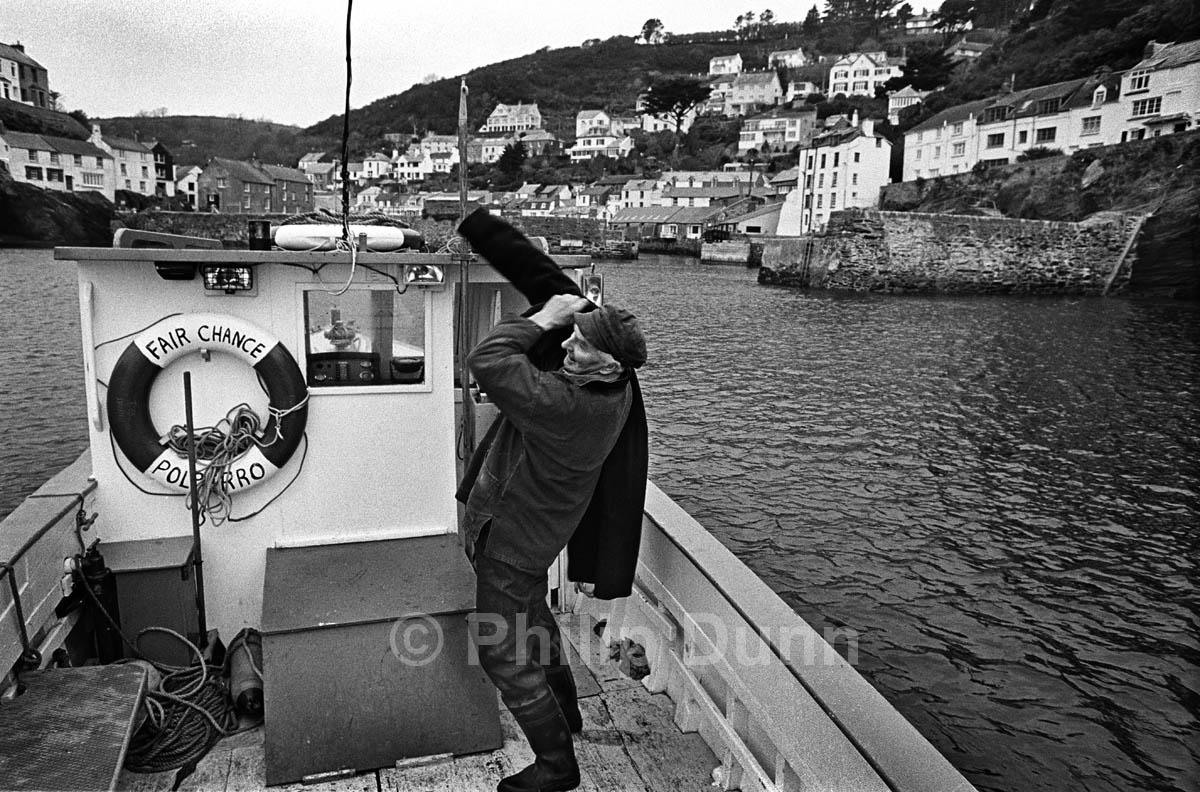 Fisherman prepares to go ashore after a day on his boat, Polperro harbour, Cornwall