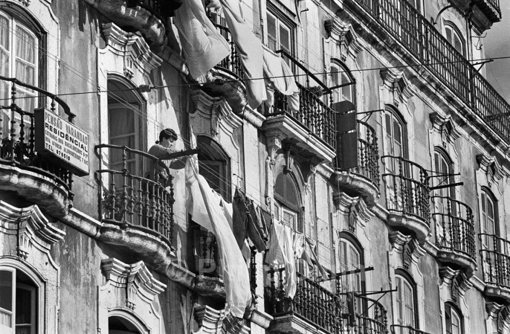 Hanging out washing from a balcony on an old, apartment blcok, Lisbon, Portugal