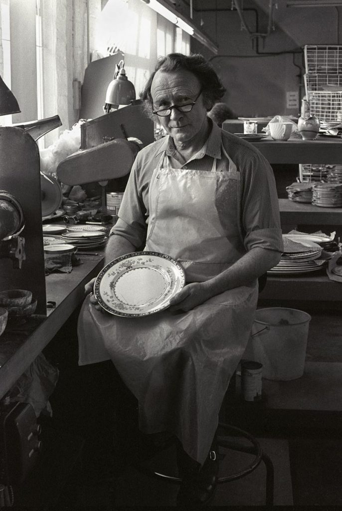 craftsman potter at Wedgwood factory in Staffordhire, He sits at his bench with a decorated plate on his lap