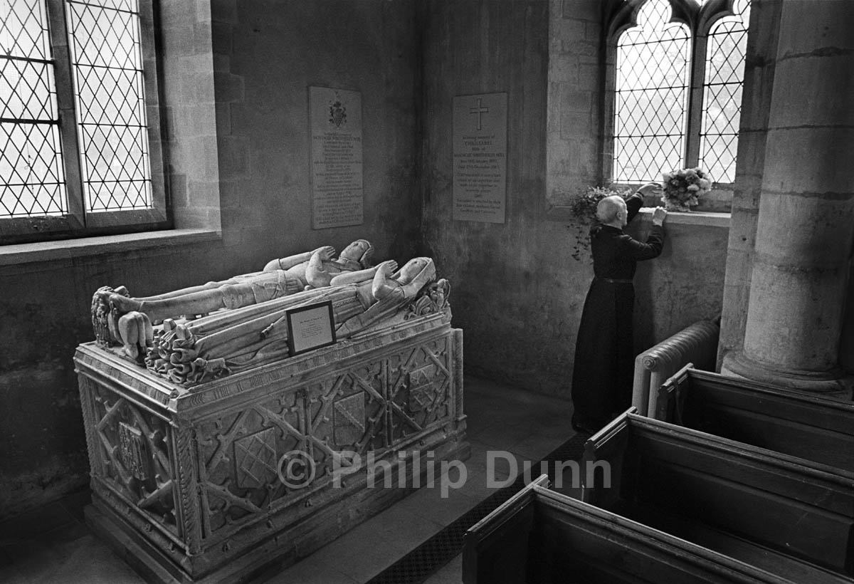 A vicar waters the flowers in church window beside ancient family tomb, Rutland. The picture is lit by the light from church windows