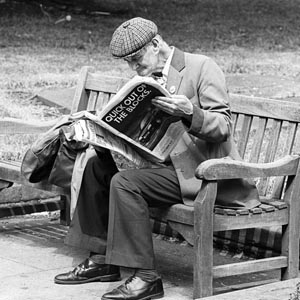 An old man wearing a cloth cap sits on a park bench in Shrewsbury reading a magazine