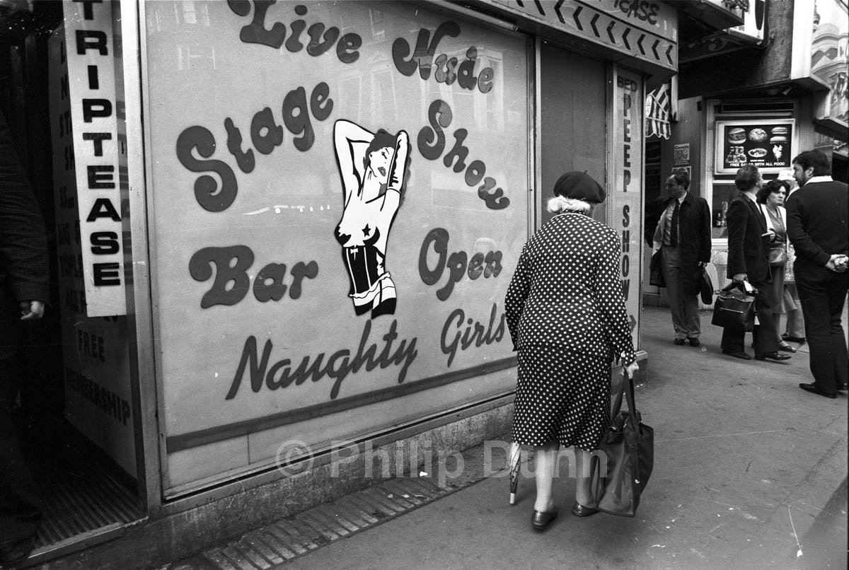 Old lady in beret passes strip club in Soho, London