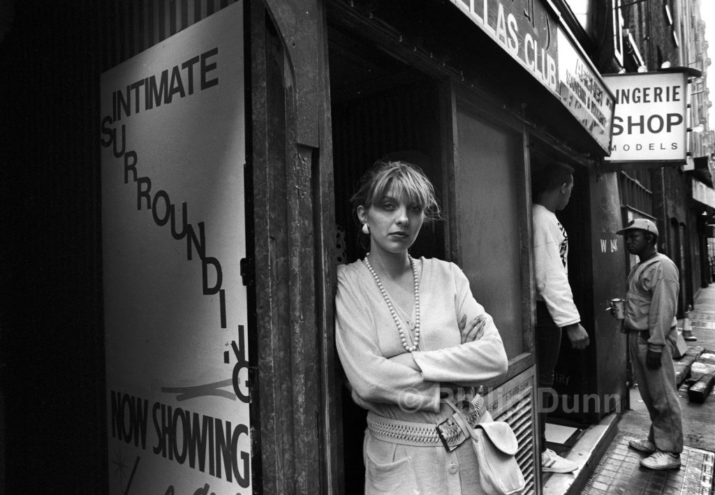 Young woman leans on doorway outside strip club, Soho