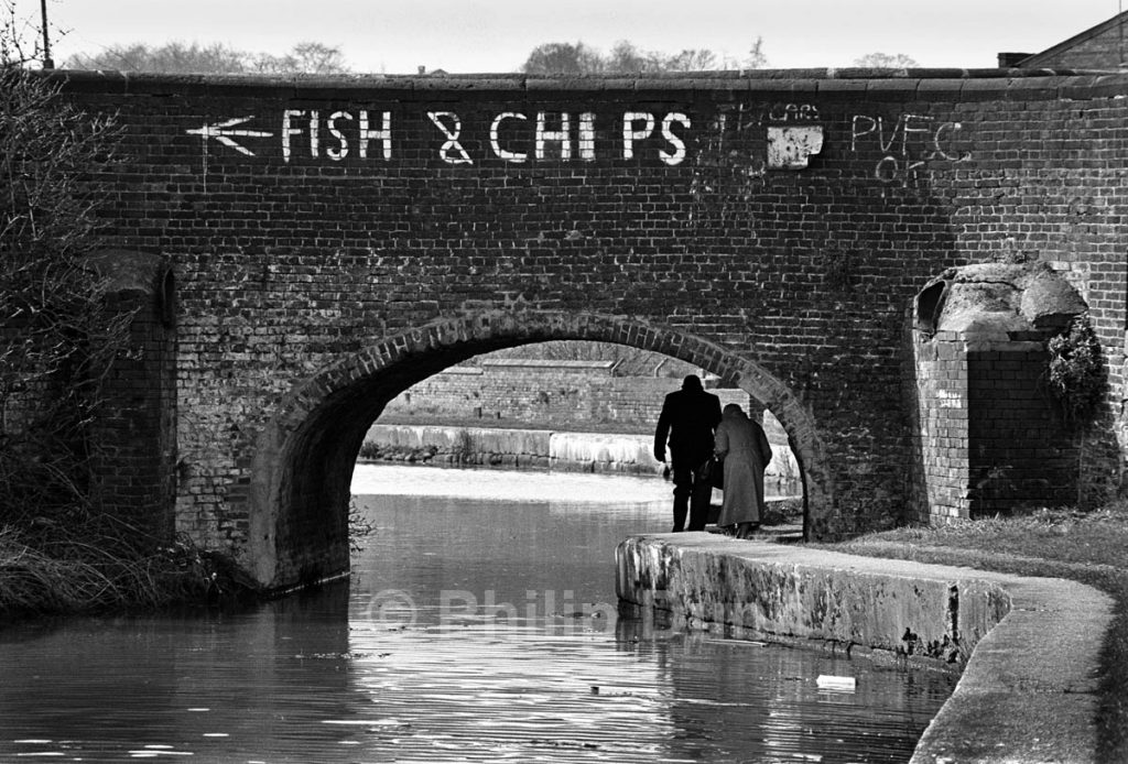 Old couple walk beneath canal bridge, Stoke on Trent. Fish and Chips is painted on the brickwork