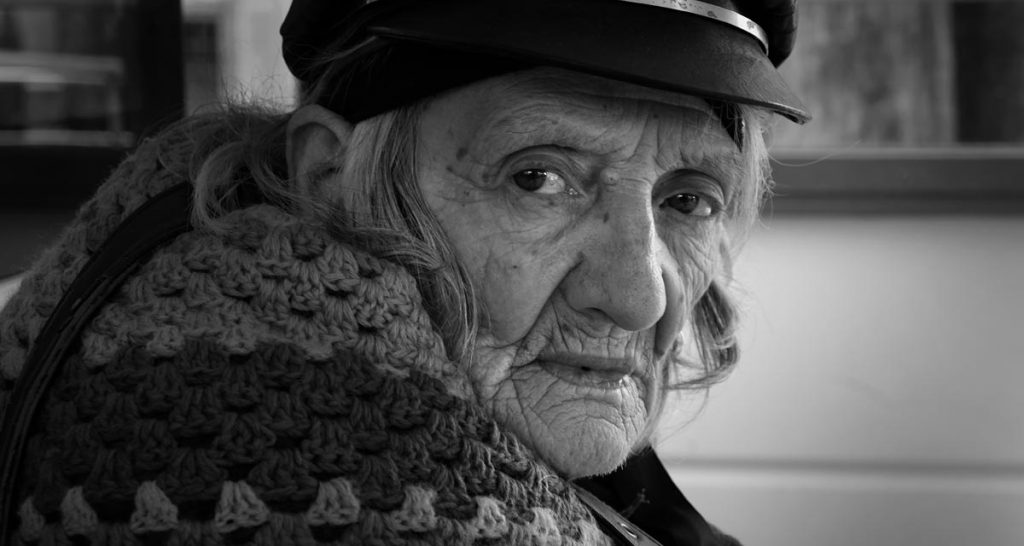 Powerful black and white street photography portrait of an old Venetian lady with lined face
