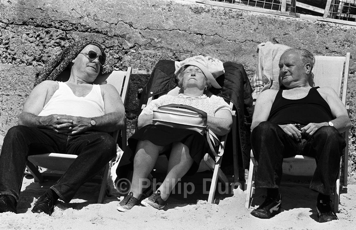 Two old men look at a sleeping old lady in deckchairs, Tenby Wales