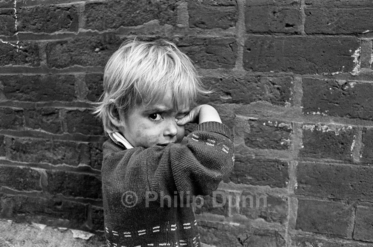 portrait of a small fair-haired boy with a dirty face, standing against a brick wall while rubbing his eye with his thumb