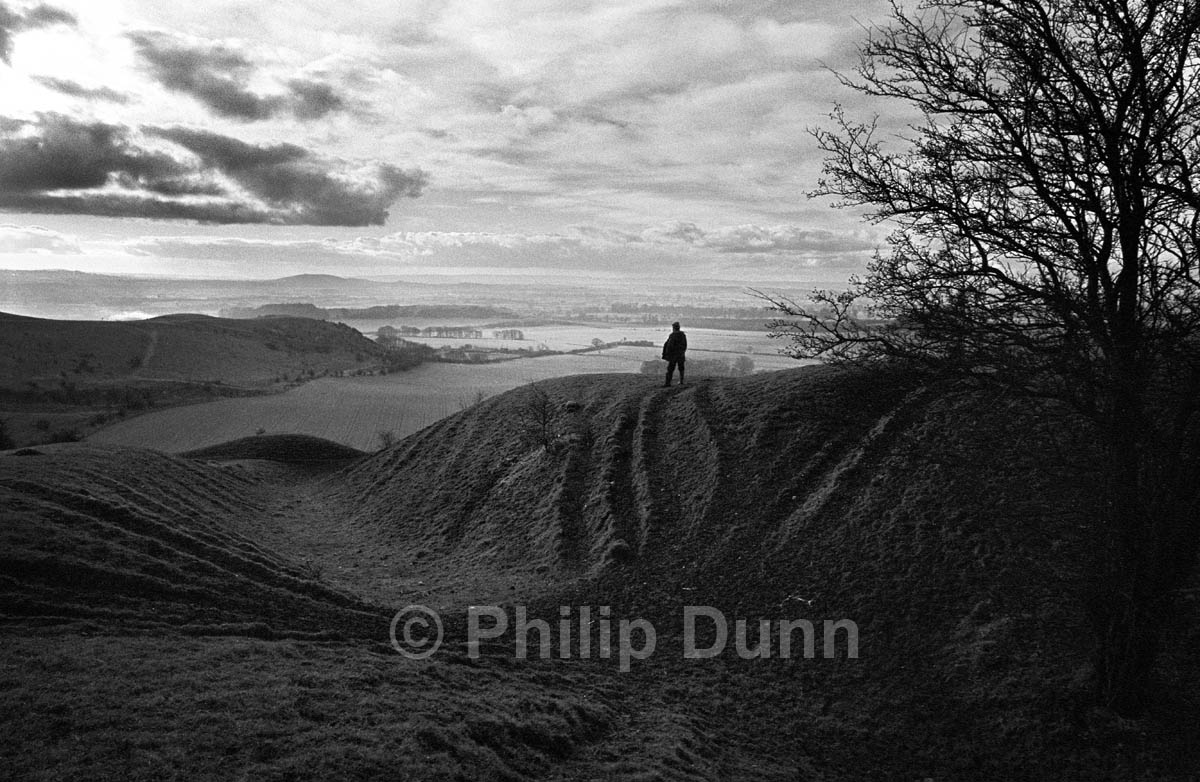 Wide angle lens shot of lone man on Wiltshire Downs at dawn