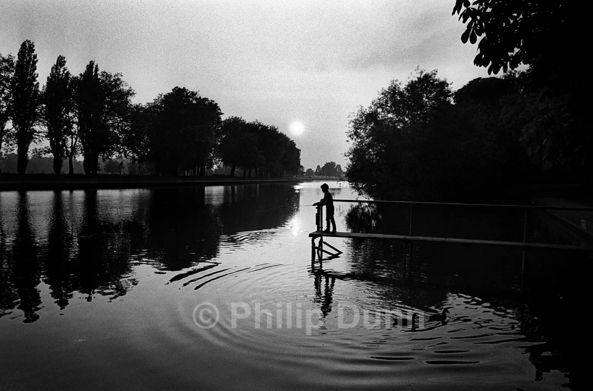 silhouette photograph of boy on small jetty on River Thames, Windsor