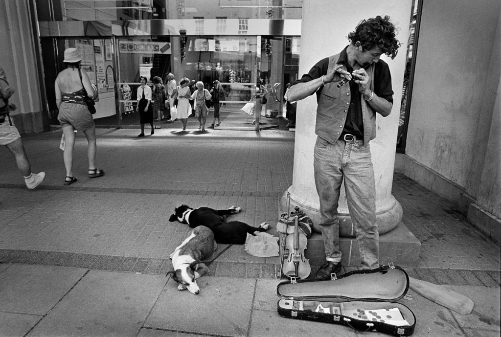 Street photography busker plays while his dogs sleep