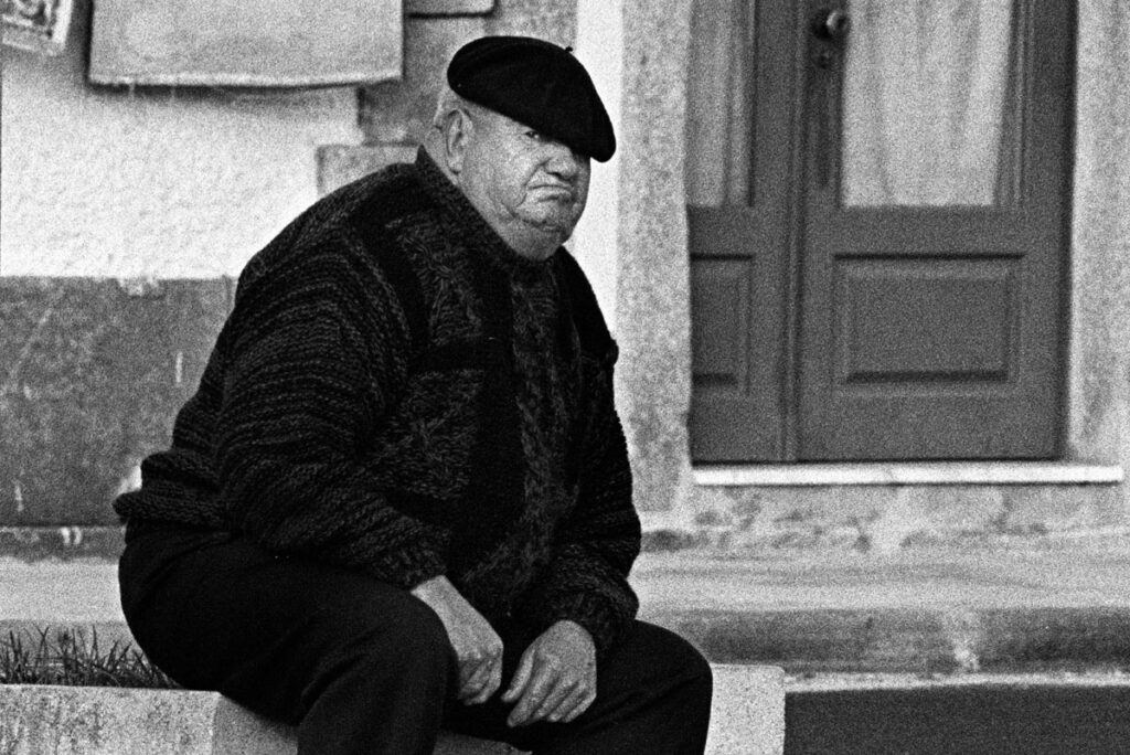 grumpy old man with beret eyes the camera in Portugal