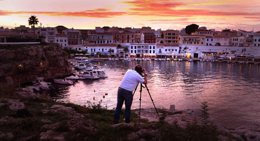 photographer working with tripod at sunset